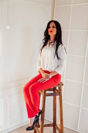 Portrait of a beautiful business woman in a red business suit in the office Stok Fotoğraf