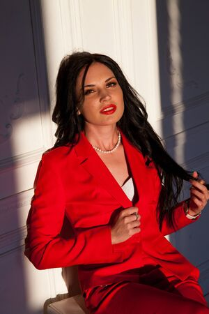 Portrait of a beautiful business woman in a red business suit in the office 版權商用圖片