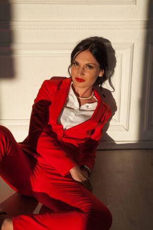 Portrait of a beautiful business woman in a red business suit in the office Stok Fotoğraf - 133083744