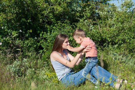 Beautiful woman plays with her beloved son on a walk
