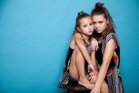 Portrait of two beautiful fashionable sisters girls on a blue background Stock Photo