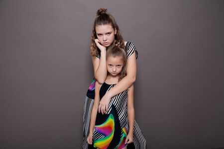 Portrait of two beautiful fashionable sisters girls on a gray background