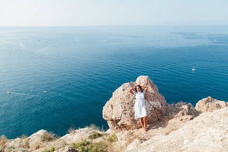 portrait of a beautiful woman with long hair on the mountain vein overlooking the sea