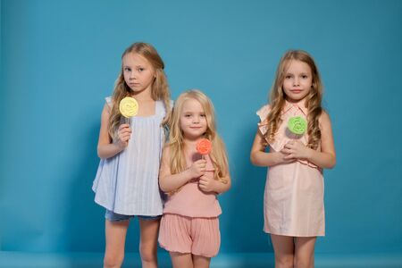 Three fashionable little girls eat candy lollipop