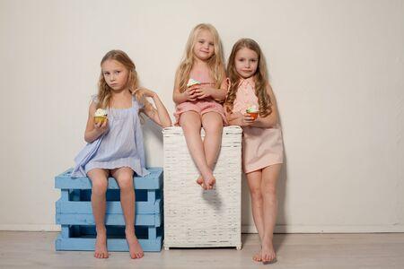 Three fashionable little girls eat candy lollipop Stockfoto
