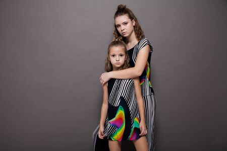 Two fashionable little sister girls of different ages Banque d'images