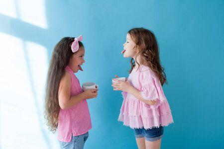 Dos niñas muestran la lengua el uno al otro