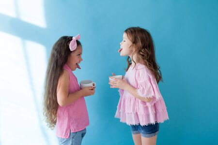 Two little girls show tongue to each other