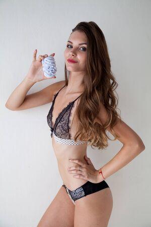 Portrait of a beautiful fashionable woman in lingerie eats a sweet cake
