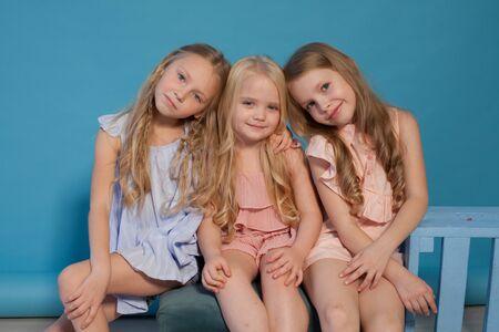Two little fashionable girls girlfriend in dresses