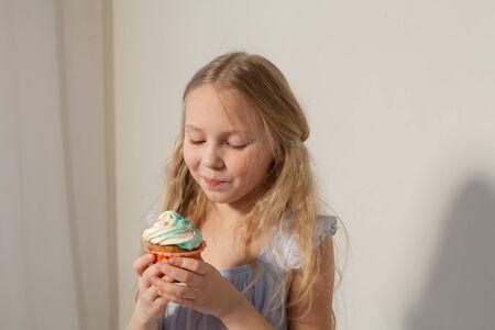 Beautiful little girl eats sweet candy cake Archivio Fotografico - 133303413