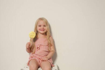 Beautiful little girl eats sweet candy cake Archivio Fotografico - 133312007