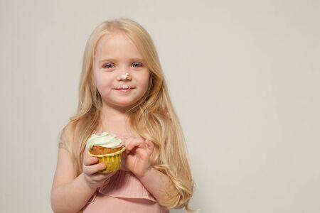 Beautiful little girl eats sweet candy cake Archivio Fotografico - 133311374