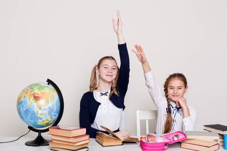 two schoolgirl girls with books and a globe in class at the desk