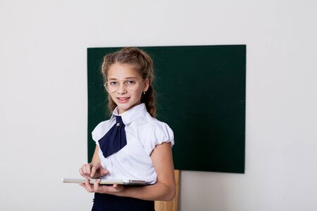 schoolgirl with internet tablet in class at green board