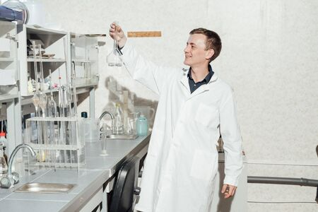 male scientist conducts chemical experiments in medical laboratory 写真素材