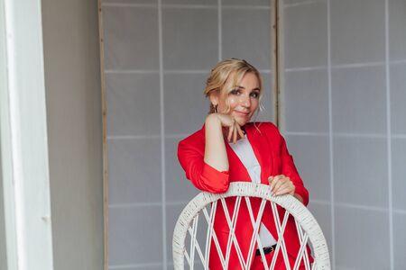 Bella donna bionda in tailleur rosso in ufficio affari Archivio Fotografico