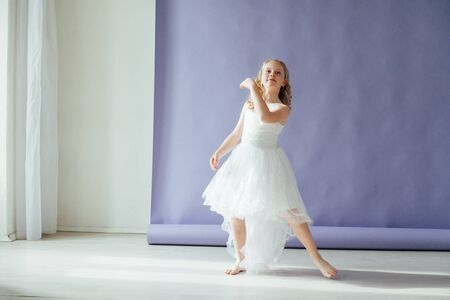 Beautiful girl of 10 years dancing in a white dress