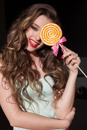 woman with long hair eats candy sweet lollipop