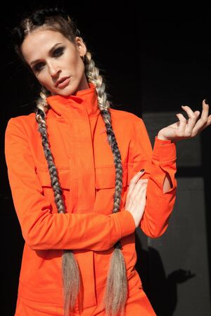 Portrait of a beautiful woman with braids in orange clothes Stock fotó