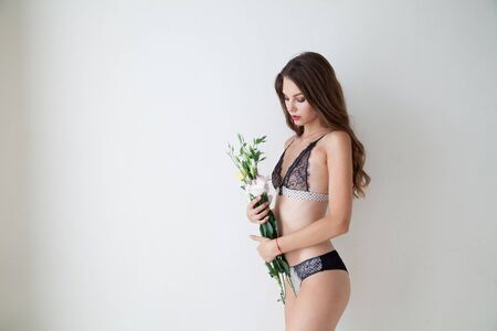 Portrait of a beautiful fashionable woman in lingerie with flowers Stock Photo