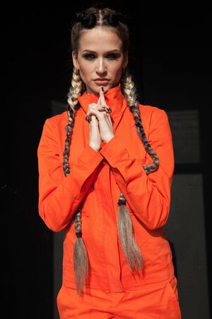 Portrait of a beautiful woman with braids in orange clothes 免版税图像
