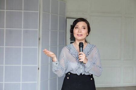 portrait of a beautiful Asian woman with a microphone in her hands