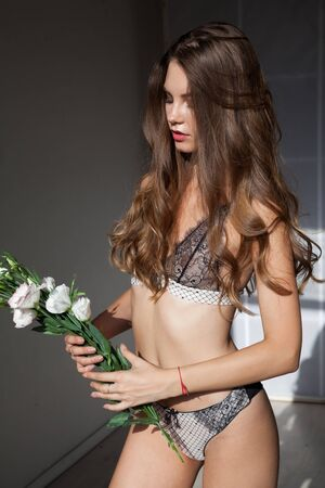 Portrait of a beautiful fashionable woman in lingerie with flowers Stockfoto
