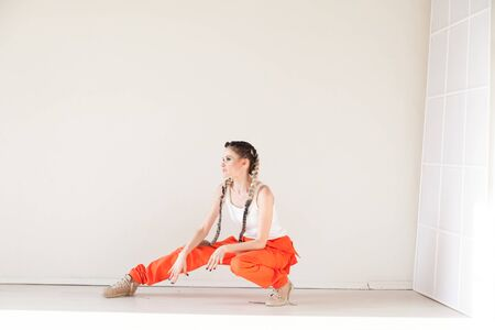 Woman with braids dances to music orange Stock fotó