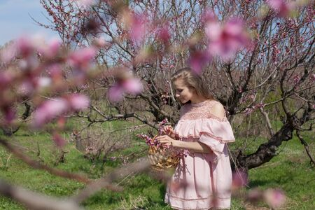 Woman blonde collects flowers in flowering garden