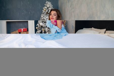 Beautiful woman in underwear Christmas tree with gifts in the bedroom on the bed