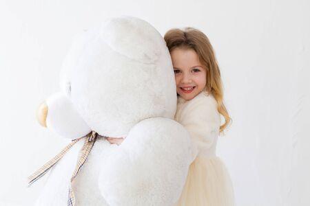 Beautiful little girl with toy big teddy bear