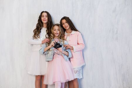 Three beautiful fashionable girl girlfriends in white pink dresses