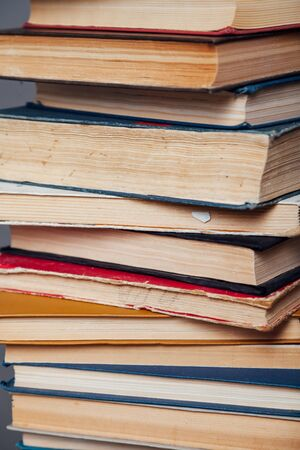 stacks of educational books against the background of the wall in the library Zdjęcie Seryjne