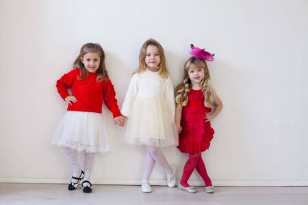 three little girls in red and white dresses for the holiday