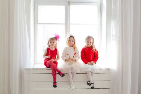 three beautiful little girls in red and white dresses at the party