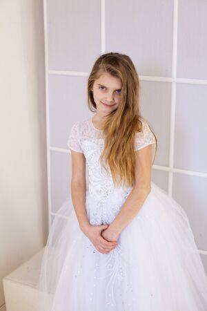 Mädchen von zwölf Jahren in einem schönen weißen Kleid