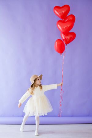 Little girl with red air in the shape of a heart