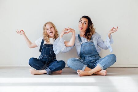Mom and daughter in denim play in white family love room Foto de archivo - 133511030