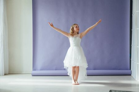 Girl in a dress dances to the music alone in the room