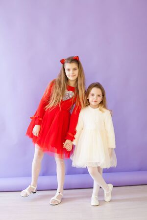 two girl girlfriends in red and white dresses on a purple background Foto de archivo - 133511126