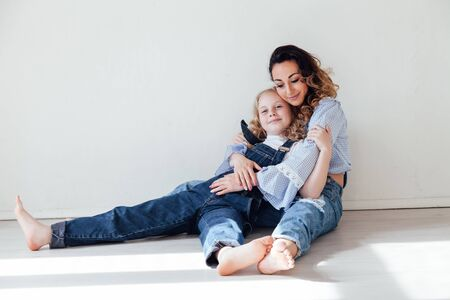 Mom and daughter in denim play in white family love room Foto de archivo - 133511192