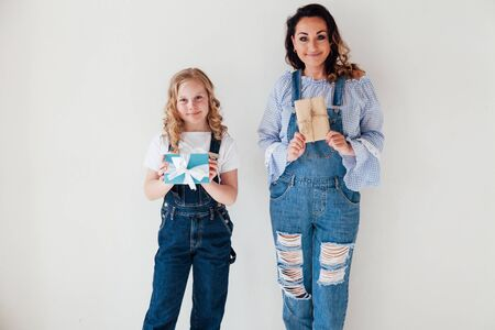 portrait of a beautiful mother and daughter in denim clothes with a gift