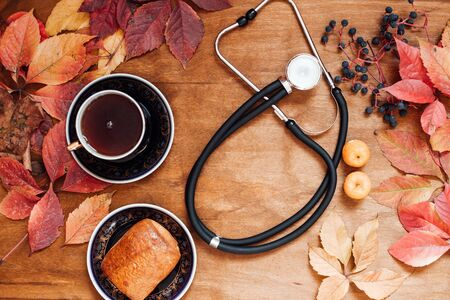 colorful leaves on wooden background medical stethoscope Stock Photo