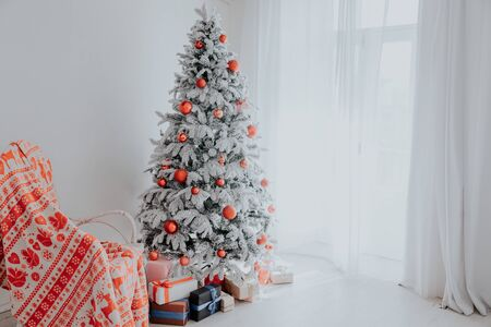 Christmas Decor Christmas tree with presents in a white room in winter Banco de Imagens