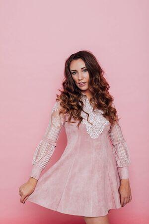 Porträt einer schönen modischen Frau mit Locken in einem rosa Kleid Standard-Bild
