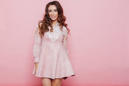Portrait of a beautiful fashionable woman with curls in a pink dress