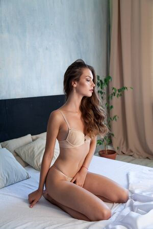 Portrait of a beautiful woman in linen in the bedroom