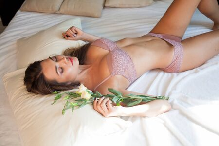 portrait of a beautiful fashionable woman in lingerie in the bedroom on the bed