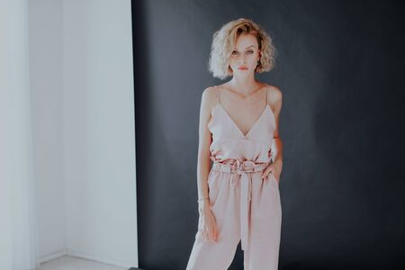 Portrait of a beautiful fashionable blonde woman in a pink in a black white room